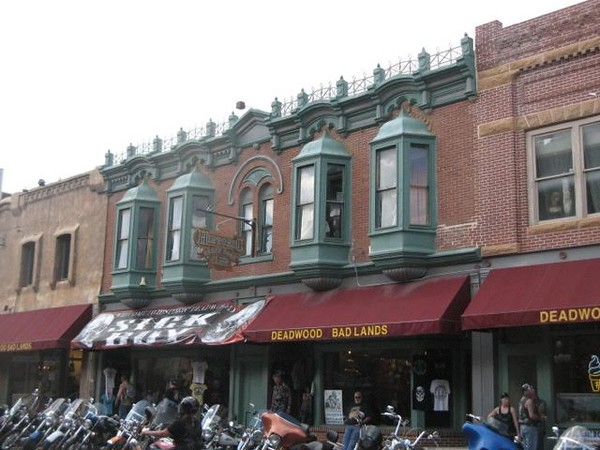 Motorcycles parked in front of brick buildings in Deadwood.