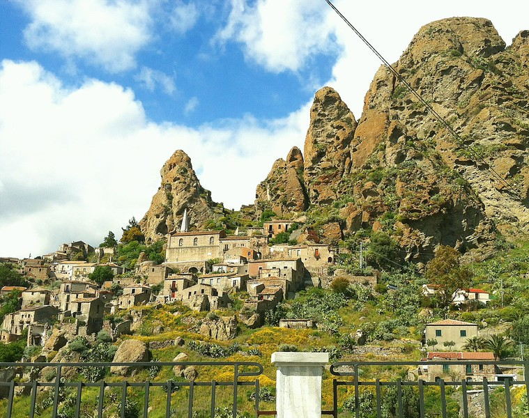 Stone houses on a hill with jagged peaks behind them in the scenic village of Pendetatillo.