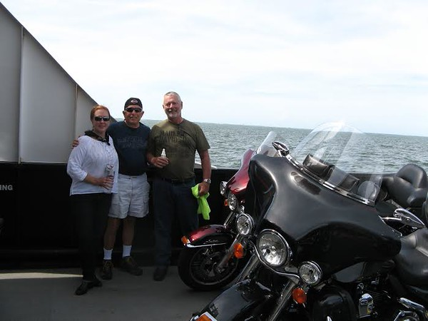 a woman and two men standing next to motorcycles on a ferry