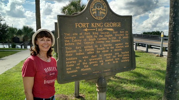 Woman standing next to Fort King George sign