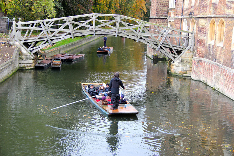 A university student punts (pushes) a boat down the river Cam in Cambridge with a wooden bridge in the distance.