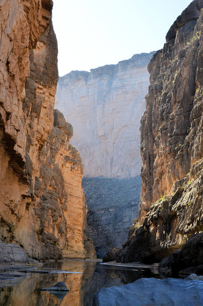 The steep, beige limestone cliffs of Santa Elena Canyon reflect in the Rio Grande River on a Big Bend National Park hiking adventure.