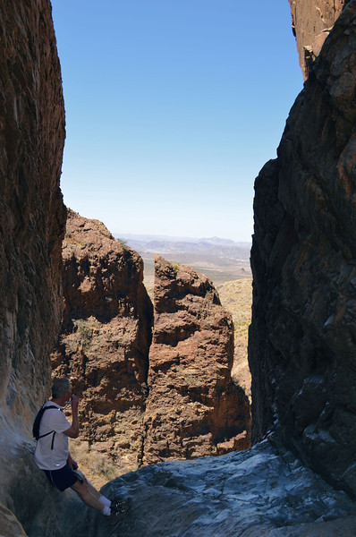 A hiker rests against the wall of the Window at the end of the rocky trail in Big Bend.