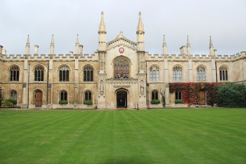The beige buildings of Corpus Christi College accented by a green lawn in Cambridge.