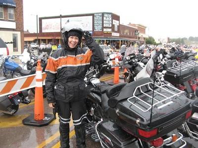 Woman motorcyclist wearing rain gear.