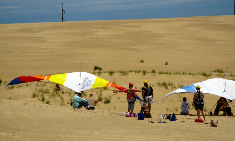 Tourists standing on a hill getting a kite lesson.