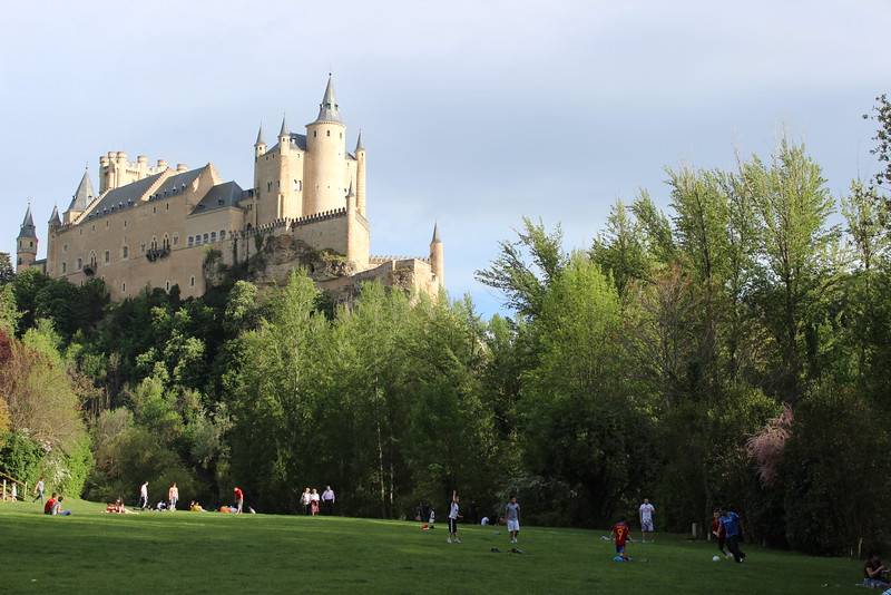 Castle spires rise about green trees and lawn in Segovia, Spain.