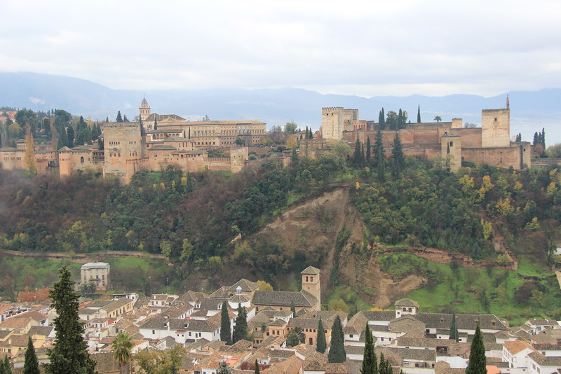 Beige moorish buildings at the Alhambra sit on a tree studded hill overlooking Granada, one of the best places to visit in Spain.