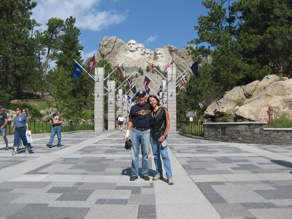 Two Boomers wearing motorcycle leathers standing in front of Mount Rushmore