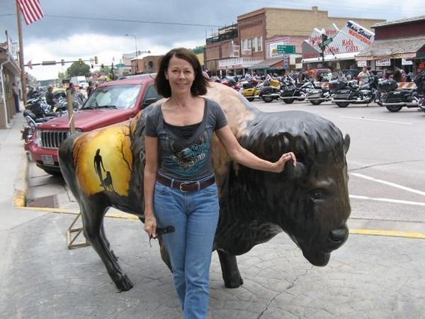 Woman posing in front of a bison statue